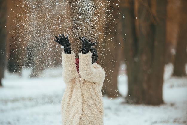 若い美しい女性が頭の上に雪を投げる