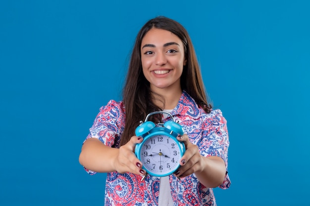 Young beautiful woman tourist holding alarm clock with a happy face and smiling over isolated blue wall