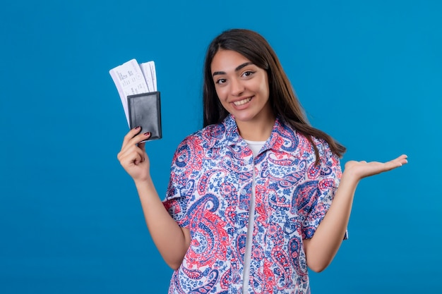 Young beautiful woman tourist holding passport with tickets looking at camera smiling cheerfully presenting with arm of hand ready to holiday standing over isolated blue background