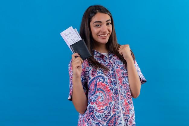 Паспорт молодой красивой женщины туристский с билетами смотря возбужденный радуясь ее успеху и победе сжимая ее кулак от радости счастливый для достижения ее цели и целей над изолятом