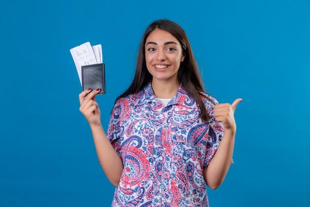 Молодая красивая женщина туристический паспорт с билетами весело улыбаясь, показывает палец вверх, готов к празднику за изолированные синей стеной