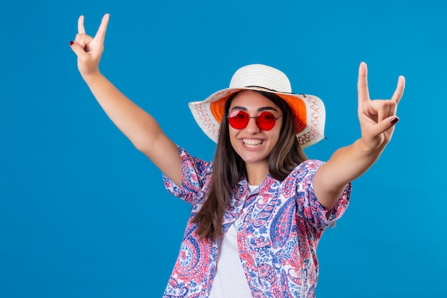 Young beautiful woman tourist wearing summer hat and red sunglasses looking joyful making rock symbols smiling cheerfully happy and positive over blue wall