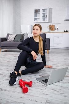 黒のトップとレギンスの若い美しい女性のトレーナーは、ラップトップと一緒に座って、検疫中に自宅でオンライントレーニング、フィットネスを見ています。健康的な生活様式。ダンベルは床にあります