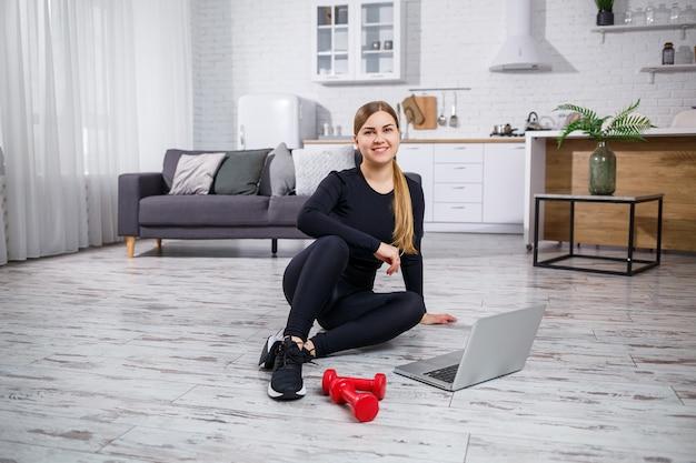 Молодая красивая женщина-тренер в черном топе и леггинсах сидит с ноутбуком и смотрит онлайн-тренировки, фитнес дома во время карантина. здоровый образ жизни. гантели на полу