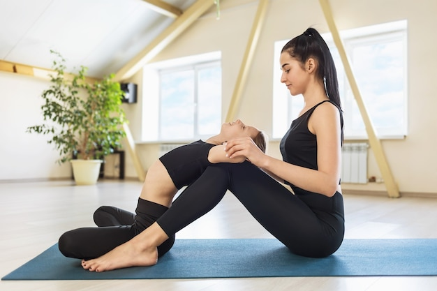 Young beautiful woman trainer practicing yoga conducts personal workout in the gym sitting on the mat rug