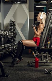 Giovane bella donna allenamento in palestra. concetto di fitness, allenamento, sport, salute