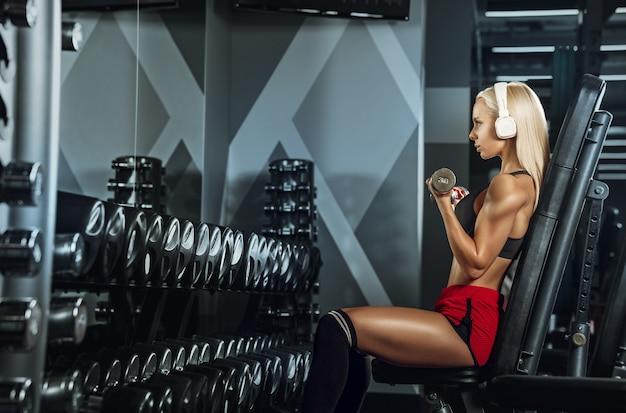Giovane bella donna allenamento in palestra. concetto di fitness, allenamento, sport, salute Foto Gratuite