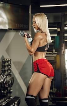 ジムでトレーニングしている若い美しい女性。フィットネス、トレーニング、スポーツ、健康の概念