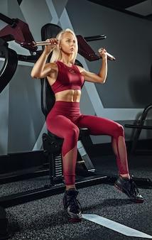 Молодая красивая женщина тренируется в тренажерном зале. концепция фитнеса, тренировки, спорта, здоровья
