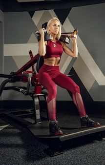 ジムでトレーニングしている若い美しい女性。