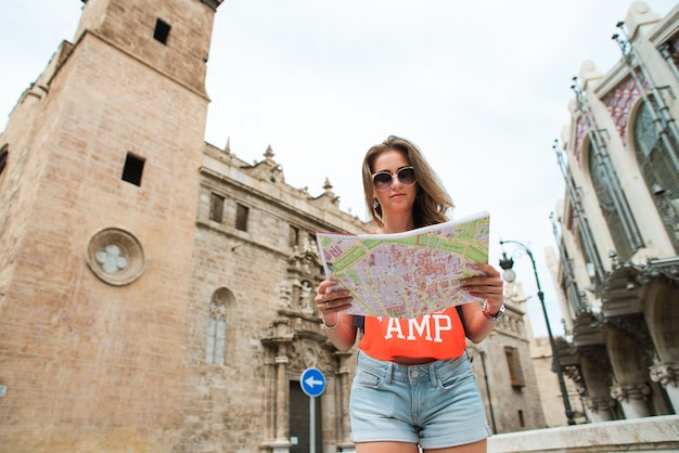 Young beautiful woman traveler with map