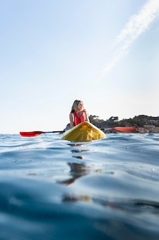 Young beautiful woman traveling by canoe