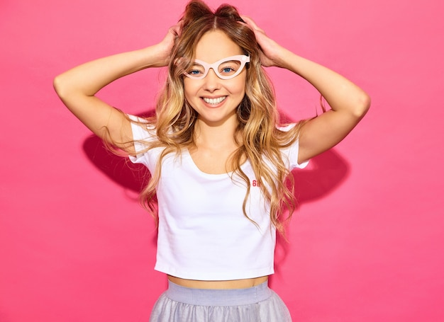 Young beautiful woman . trendy woman in casual summer clothes in fake props sunglasses. positive female emotion facial expression body language. funny model playing with her hair on pi
