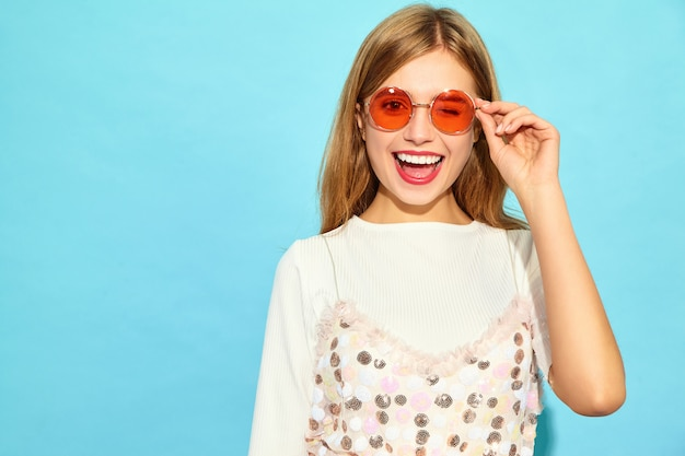 Young beautiful woman .trendy woman in casual summer clothes winking in sunglasses. positive female emotion facial expression body language. funny model isolated on blue wall