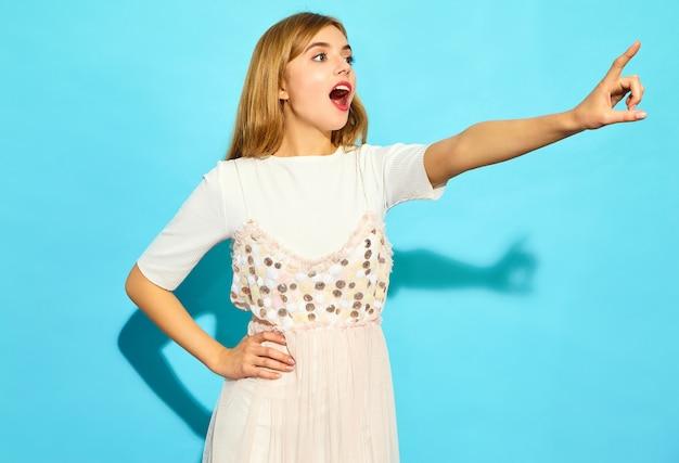 若い美しい女性。カジュアルな夏服のトレンディな女性。青い壁に分離された店の売り上げ高を指している肯定的な女性モデル