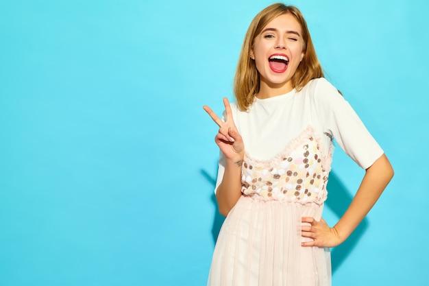 若い美しい女性。カジュアルな夏服のトレンディな女性。まばたきと青い壁に分離されたピースサインを示す肯定的な女性モデル