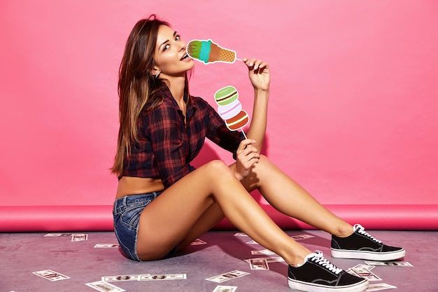 若い美しい女性。ピンクの壁の近くの床に座ってカジュアルな夏服でトレンディな女性。小道具甘いアイスクリームとマカロンを食べるポジティブモデル。