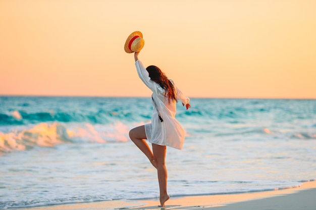 Young beautiful woman on tropical beach in sunset.