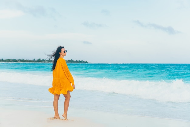Young beautiful woman on tropical seashore in sunset.