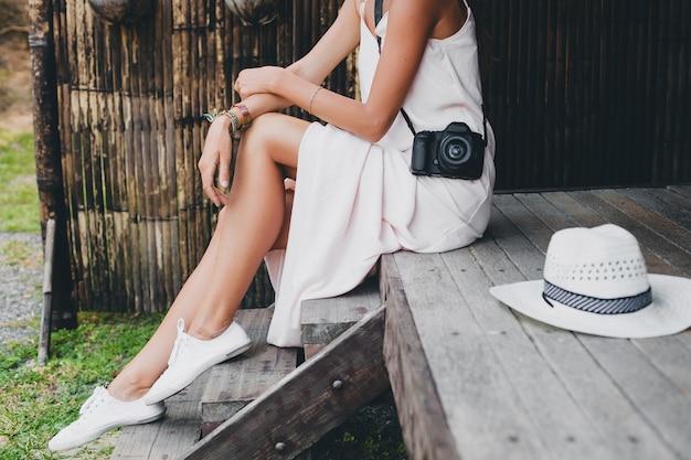 Giovane bella donna in vacanza tropicale in asia, stile estivo, abito boho bianco, scarpe da ginnastica, fotocamera digitale, viaggiatore, cappello di paglia, gambe da vicino i dettagli