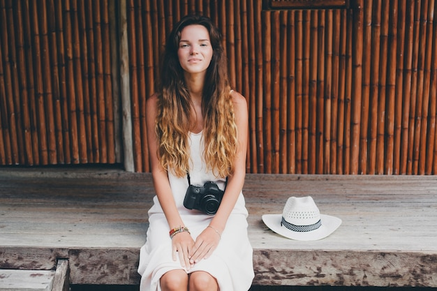 Young beautiful woman on tropical vacation in asia, summer style, white boho dress, sneakers, digital photo camera, traveler, straw hat, smiling, boho