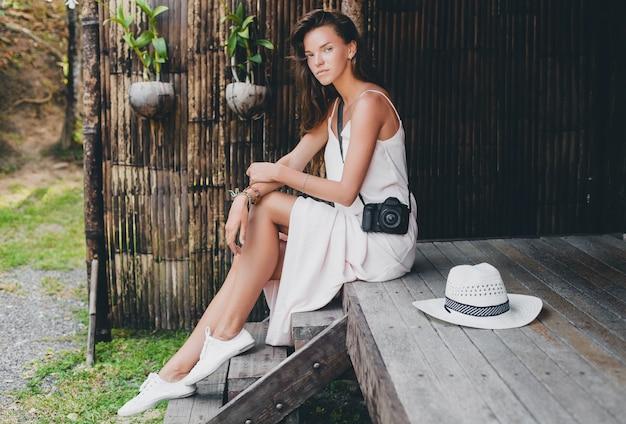 Giovane bella donna in vacanza tropicale in asia, stile estivo, abito boho bianco, scarpe da ginnastica, fotocamera digitale, viaggiatore, cappello di paglia, sorridente, boho