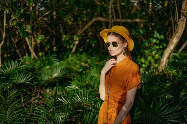 Young beautiful woman in the tropics jungle with hat walks in the park, naturalist