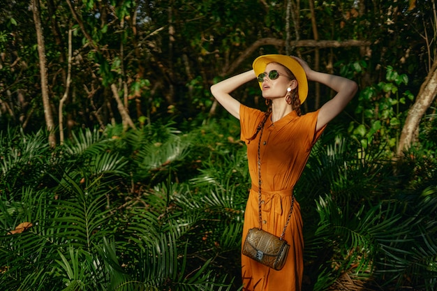 Young beautiful woman in the tropics jungle with hat walks in the park