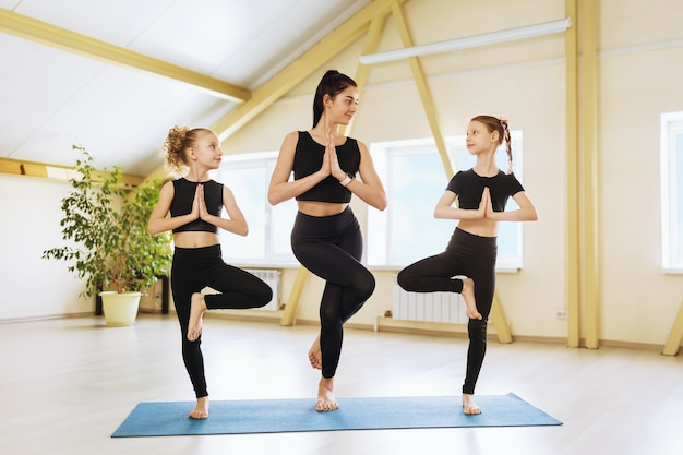Young beautiful woman universal yoga trainer and two little girls in black sportswear perform