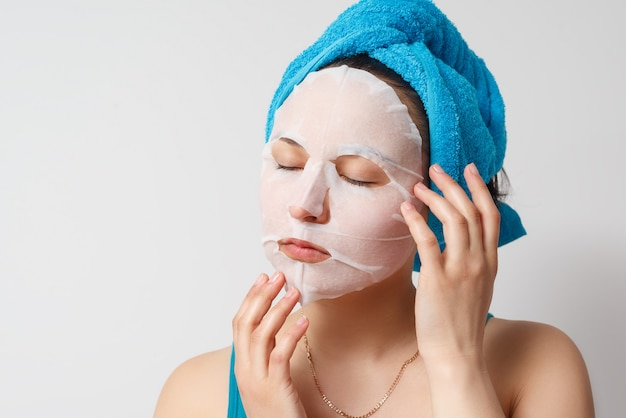 A young beautiful woman uses a moisturizing cosmetic fabric face mask with a towel
