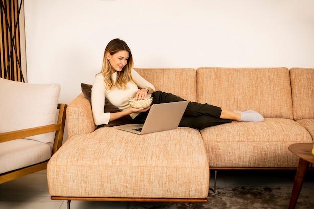 自宅のソファでノートパソコンを使用して若い美しい女性