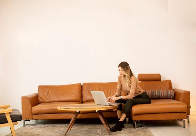 Молодая красивая женщина, используя ноутбук на диване у себя дома