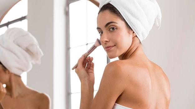 Молодая красивая женщина с помощью кисти для макияжа