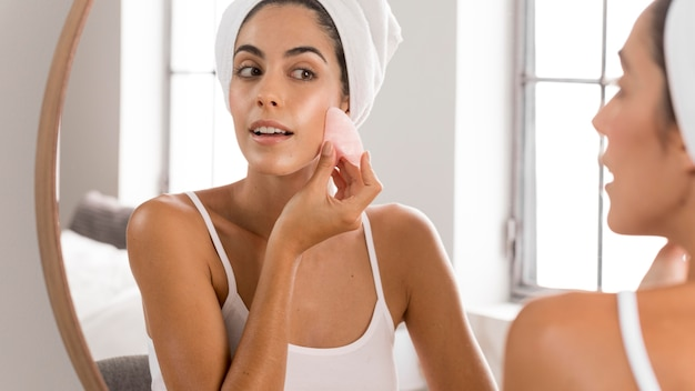 Young beautiful woman using foundation cream