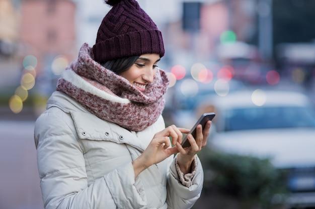 彼女の携帯電話を使用して若い美しい女性