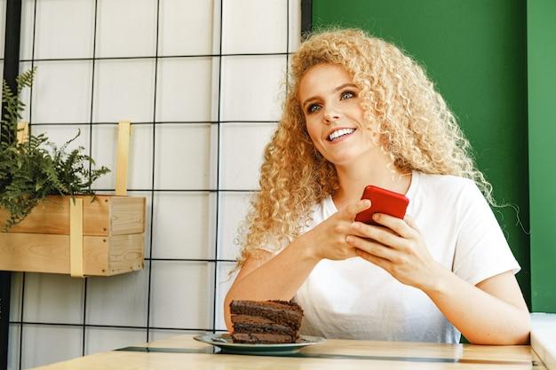 Молодая красивая женщина, используя свой телефон в кафе
