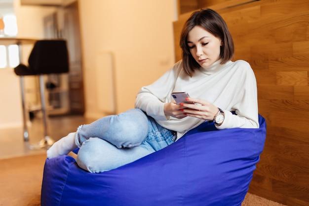 Молодая красивая женщина, используя ее телефон, сидя в кресле мешок