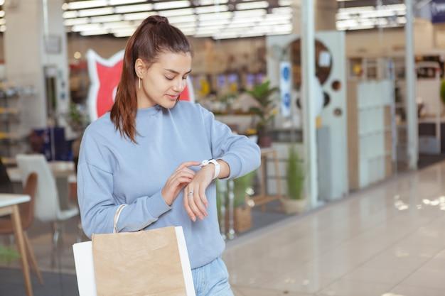 Молодая красивая женщина, используя ее умные часы при совершении покупок в торговом центре, скопируйте пространства