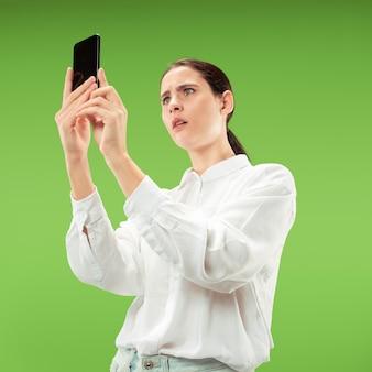 緑の色のスタジオで携帯電話スタジオを使用して若い美しい女性。