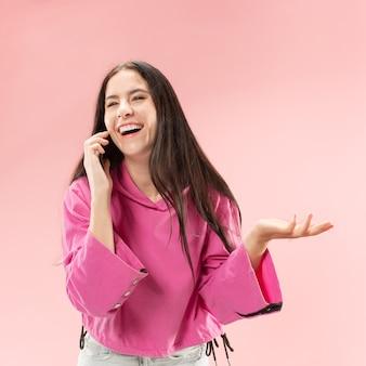 ピンク色のスタジオの背景に携帯電話スタジオを使用して若い美しい女性。人間の顔の感情の概念。トレンディな色