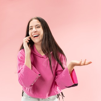 Young beautiful woman using mobile phone studio on pink color studio background. human facial emotions concept. trendy colors