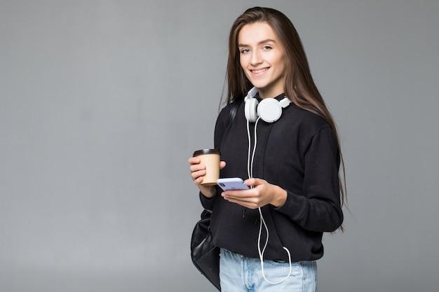 회색 벽에 고립 된 스마트 휴대 전화를 사용하여 젊은 아름 다운 여자
