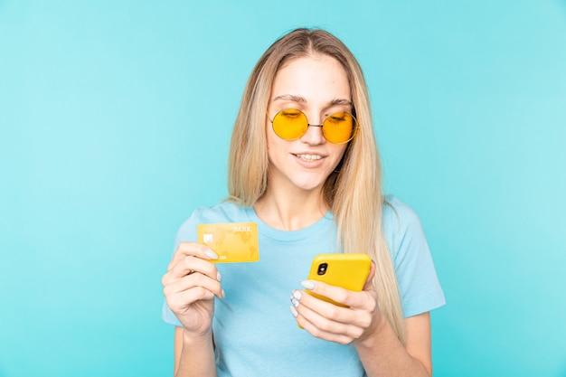 Молодая красивая женщина с помощью смартфона и кредитной карты для покупок в интернете. электронные платежи.