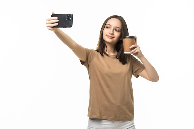 Молодая красивая женщина, используя время селфи смартфона, держа чашку кофе и мобильный телефон изолированного на белом