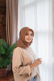 ベールに包まれた若い美しい女性がカーテンの窓の近くに立っているカメラに見える