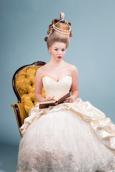 Young beautiful woman in vintage victorian dress with complicated hairstyle sitting in a chair