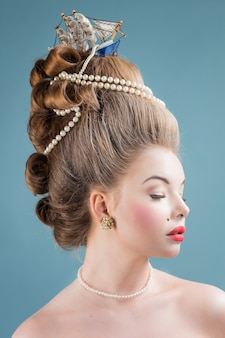 Young beautiful woman in vintage victorian dress with complicated hairstyle