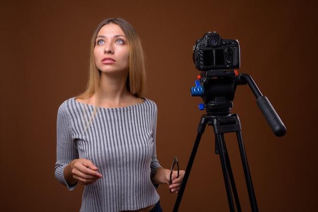 スタジオでデジタル一眼レフカメラでvlogする若い美しい女性