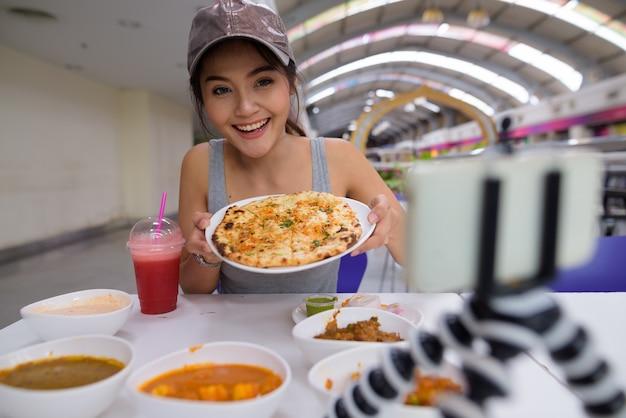 Молодая красивая женщина ведет видеоблог с мобильного телефона в ресторане