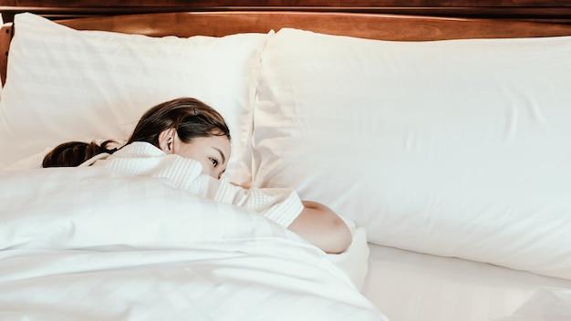Молодая красивая женщина просыпается в постели после хорошего сна прошлой ночью.